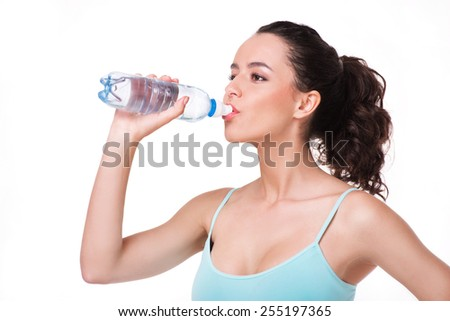Young sporty woman drinking water after fitness, isolated on white background - stock photo