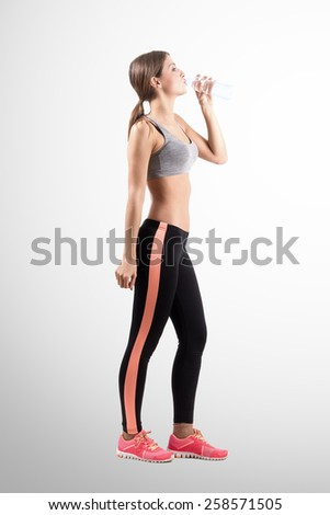 Young sporty woman drinking water from the bottle. Full body length portrait over retro background with vignette. - stock photo
