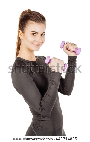 Young  sporty woman holds in hands dumbbells looking at camera, smiling. isolated on white background. fitness, sport and health concept  - stock photo