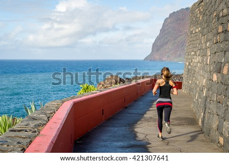 Young sporty woman in running on walking path near the ocean. Camara de Lobos, Madeira island, Portugal