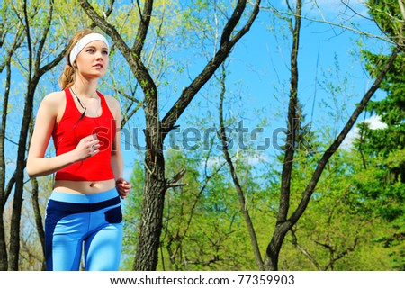 Young sporty woman is jogging outdoor. - stock photo