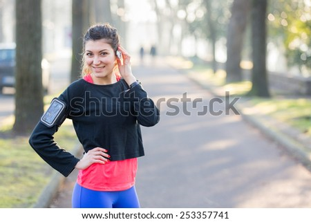 Young Sporty Woman Portrait at Park. She is Standing with Hands on Hips, Wearing a Black Sweatshirt. She has a Smart Phone Holder on her Arm and Listen Music with Earphones. - stock photo