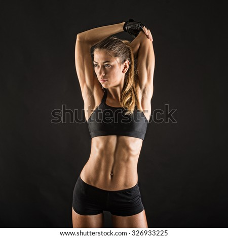 Young sporty woman portrait doing stretching against black background. Grunge effect. - stock photo