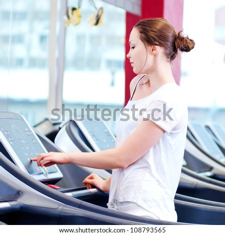 Young sporty woman run on machine in the gym centre - stock photo