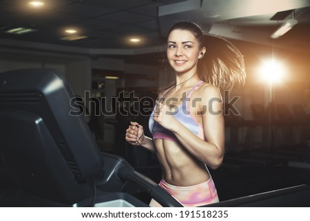 Young sporty woman running on machine in the gym and listening music in headphones - stock photo