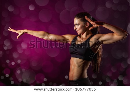 Young sporty woman shows a hand forward. The background bokeh - stock photo