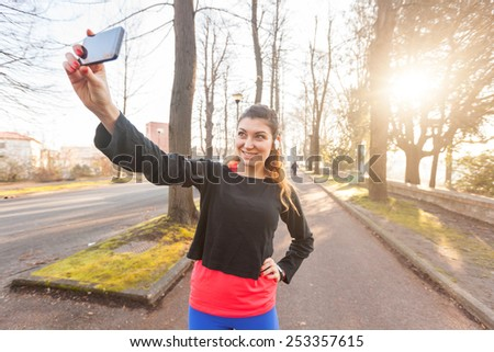 Young Sporty Woman Taking a Selfie at Park. She is Looking at Smart Phone, Wearing a Black Sweatshirt. She has a Smart Phone Holder on her Arm and Listen Music with Earphones. - stock photo