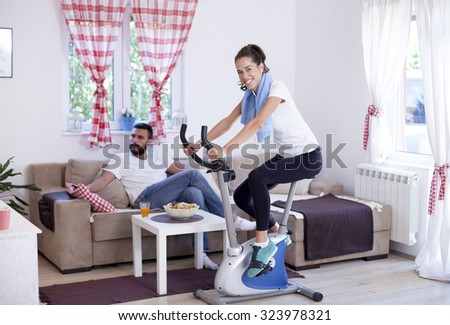 Young sporty woman training on exercise bike in the living room while husband is relaxing and watching tv