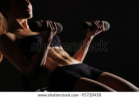 Young sporty woman training with the dumbbell - stock photo