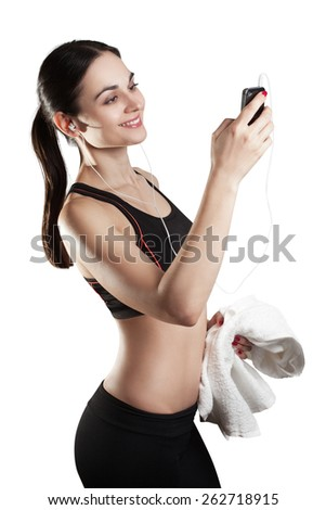 Young sporty woman typing a message after a training, isolated on white - stock photo