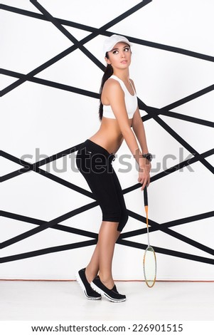 Young sporty woman wearing sport clothes posing with badminton racket - stock photo