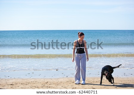 Young sporty woman with a dog on the beach - stock photo