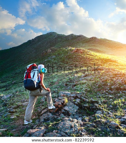 Young sporty woman with backpack walking through rocky land to the top a mountain - stock photo