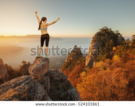 Young sporty woman with raised arms on top of the mountain. Female stay on the top of mountain under sunlight.