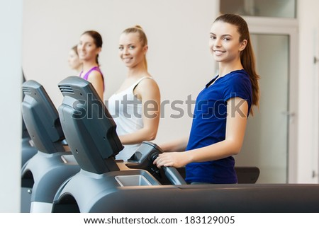 young sporty women run on machine in the gym centre - stock photo
