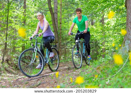 Young spoty active cople biking in nature. Active lifestyle. Activities and recreation outdoors. - stock photo