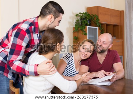 Young spouses sitting with documents and asking friends for advice
