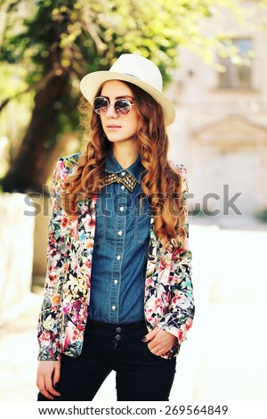 Young spring fashion woman in spring garden. Springtime. Trendy hipster girl wearing vintage sunglasses, jeans shirt, white hat and jacket, curly long hair.  - stock photo