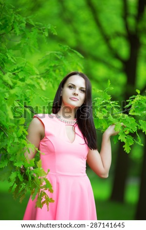 Young spring fashion woman. Trendy girl in the branches of the oak in the spring summer garden. Springtime or summertime. Lady in spring landscape background.  - stock photo