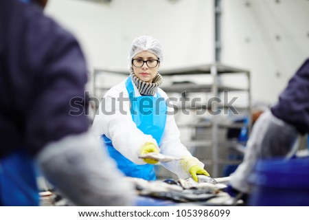 Young staff in uniform and her colleagues sorting frosted fish before processing