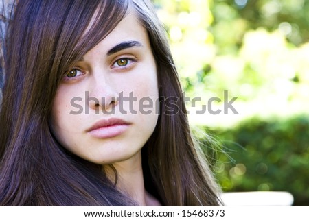 Young staring woman with green nature color as background - stock photo