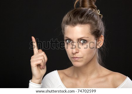 Young stern female pointing with her finger up - stock photo