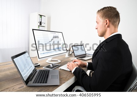 Young Stock Market Broker Looking At Graphs On Computer In Office