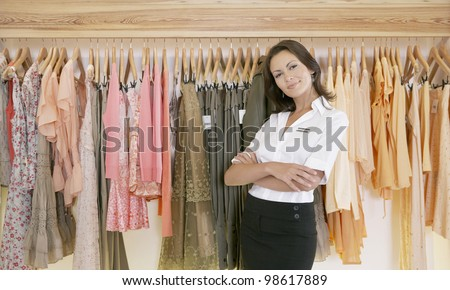 Young store attendant standing proudly by a line of clothes in a fashion store. - stock photo