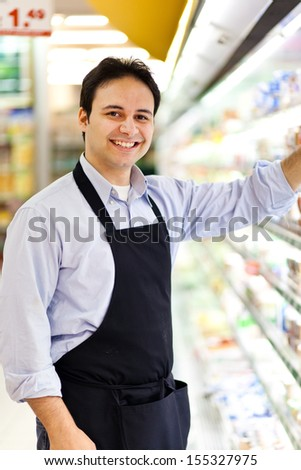Young storekeeper smiling - stock photo
