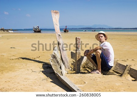 Young stranger sitting on the shattered boat and looking around - stock photo