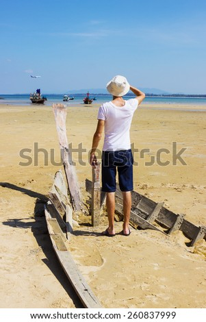 Young stranger standing on the shattered boat and looks into the distance - stock photo