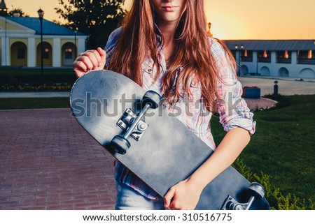 Young street fashion cute girl is holding skateboard in evening summer time smile hipster style photo color filter toned colorized image front view. Redhair teen girl with longboard in her hands - stock photo