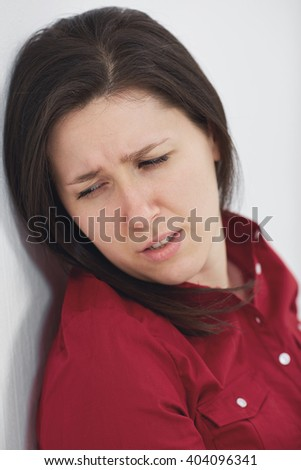 Young stressed and depressed woman, shoot against white wall - stock photo