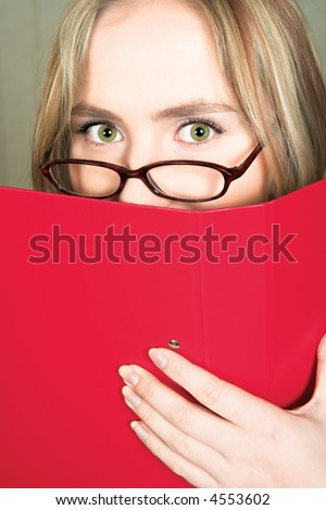 Young stressed blond business woman with large green eyes in glasses hiding behind a red folder - stock photo