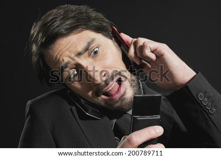 Young stressed businessman using two mobile phones close up - stock photo