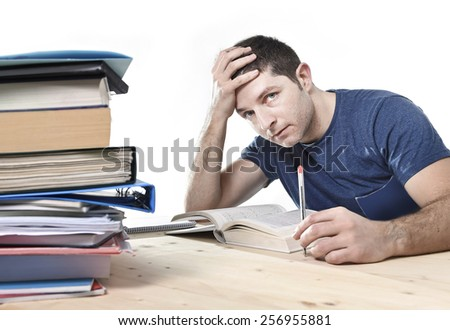 young stressed Caucasian student studying pile of books on library desk preparing exam in stress feeling tired and overwhelmed in youth education concept - stock photo