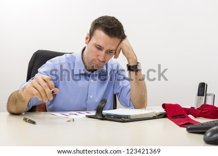 Young stressed manager analyzing some charts with hand at his temple. - stock photo