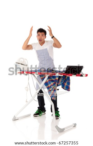 Young stressed Nepalese man with iron and laptop on the ironing-board. Studio shot, white background. - stock photo