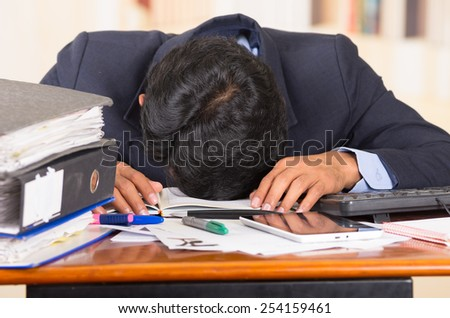 young stressed overwhelmed business man with piles of folders sleeping on his desk  - stock photo