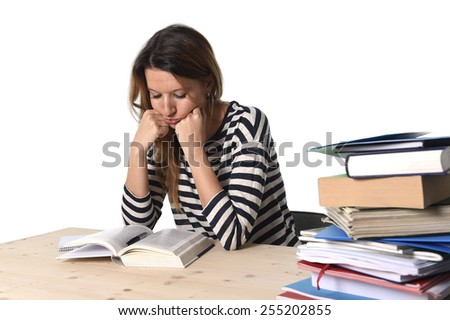 young stressed student girl studying pile of books on library desk preparing MBA test or exam in stress feeling tired and overwhelmed in youth education concept  - stock photo