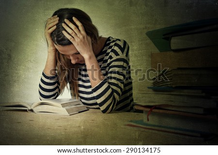 young stressed student girl studying pile of books on library desk preparing MBA test or exam in stress feeling tired and overwhelmed in youth education concept grunge messy background style - stock photo