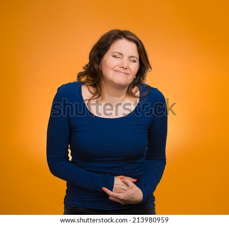 Young stressed woman having stomach pain, hands on belly, having bad aches, pains, isolated orange background. Food poisoning, influenza, cramps. Negative emotions, facial expressions, feelings - stock photo