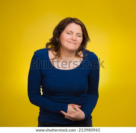Young stressed woman having stomach pain, hands on belly, having bad aches, pains, isolated yellow background. Food poisoning, influenza, cramps. Negative emotions, facial expressions, feelings - stock photo