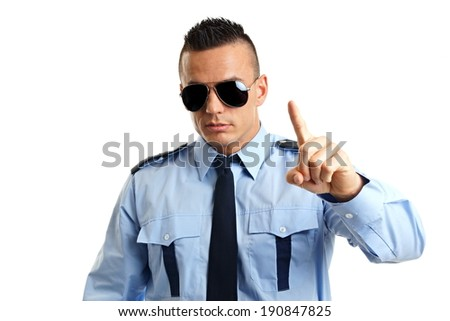 Young strict man in police uniform shows with finger on you