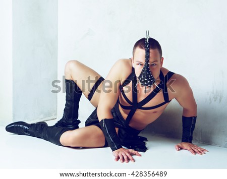 young strip dancer wearing a leather costume, in the studio - stock photo