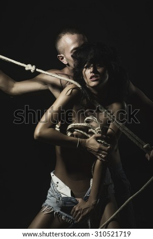 Young stripped couple of sexy pretty tan girl in jeans shorts and man with strong muscular beautiful body with rope standing close to each other feeling passion on black background, vertical picture - stock photo