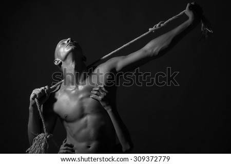 Young stripped handsome man with sexy strong muscular body with long durable rope and female hands standing on studio background black and white, horizontal picture