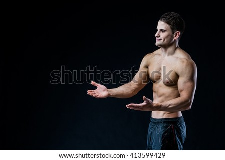 Young strong athlete on dark background looking to the blank space