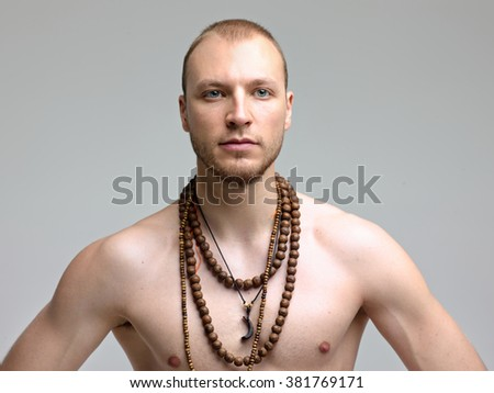 Young, strong handsome man with naked torso posing in the studio on a gray background. On the neck Tibetan necklace