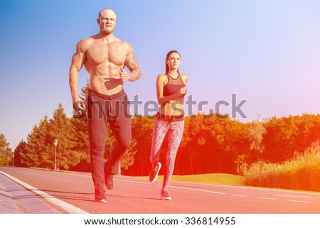 Young strong male and female  fitness models outdoors in beautiful landscape. Man and woman running in park at sunset - stock photo